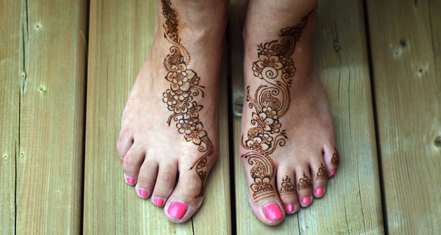 Intricate henna design on two feet side by side